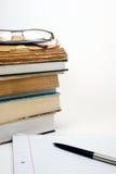 Gläser, Bücher, Feder und Papier Stockfotografie
