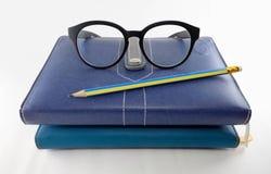 Gläser, Bleistift und Stapel von Büchern Lizenzfreies Stockfoto