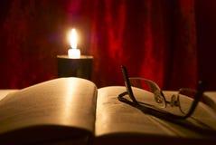 Gläser, Buch und Kerze Stockbild