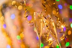 Gläser Champagner mit Hintergrund des strahlenden Golds Lizenzfreie Stockfotografie