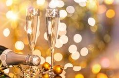 Gläser Champagner mit Hintergrund des strahlenden Golds Stockfotografie