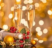 Gläser Champagner mit Hintergrund des strahlenden Golds Stockbild