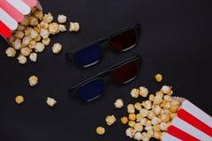 Gläser 3D und Popcorn mit Tastatur auf einer Draufsicht des schwarzen Hintergrundes stockfotografie