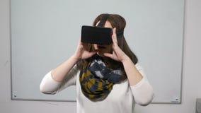 Gläser der Frauenprüfungs-virtuellen Realität in einem Klassenzimmer mit whiteboard hinten - VR stock video footage