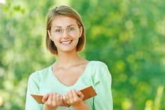 Gläser der jungen Frau lasen Buch Lizenzfreie Stockfotografie