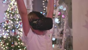 Gläser der virtuellen Realität Ein Jugendlicher, der ein Computerspiel mit einem Sturzhelm spielt stock video