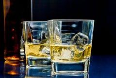 Gläser des alkoholischen Getränks mit Eis auf Blaulicht Lizenzfreies Stockbild