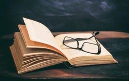 Gläser des alten Buches und des Auges auf Tafelhintergrund Stockfoto