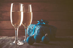 Gläser des Champagners und des Geschenks auf hölzernem Hintergrund Stockfotografie