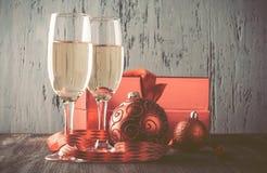 Gläser des Champagners und des Geschenks auf hölzernem Hintergrund Lizenzfreies Stockbild