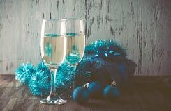 Gläser des Champagners und des Geschenks auf hölzernem Hintergrund Stockbild