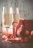 Gläser des Champagners und des Geschenks auf hölzernem Hintergrund Lizenzfreie Stockfotografie