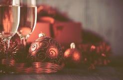 Gläser des Champagners und des Geschenks auf hölzernem Hintergrund Stockbilder