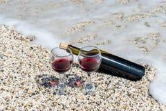 Gläser des Rotweins und der Flasche auf dem Strand am Sommertag lizenzfreie stockfotos