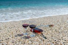Gläser des Rotweins und der Flasche auf dem Strand am sonnigen Tag des Sommers Lizenzfreies Stockbild
