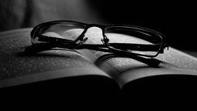 Gläser, die auf dem Buch liegen Lizenzfreies Stockfoto