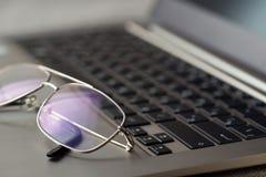 Gläser, die auf der Laptoptastatur liegen Stockfotografie