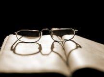 Gläser, die auf einem Buch mit einem Schatten in Form eines Herzens liegen lizenzfreie stockbilder