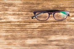 Gläser für die Korrektur von Visionslüge auf einem dunklen hölzernen Hintergrund stockfotografie