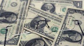Gläser für Visionskorrektur und ein kleiner Stapel von Dollar Lizenzfreie Stockfotografie