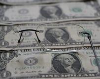 Gläser für Visionskorrektur und ein kleiner Stapel von Dollar Stockfotos