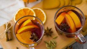 Gläser heißer Glühwein mit Orange und Gewürzen stock video