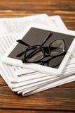 Gläser, Kaffeetasse, digitale Tablette und Zeitungspapier auf Holztisch lizenzfreies stockfoto