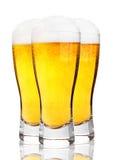 Gläser kaltes Bier mit Schaum und Schaum auf Weiß Stockbilder