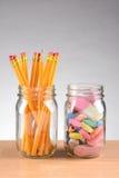 Gläser mit Bleistiften und Radiergummis Lizenzfreie Stockfotos