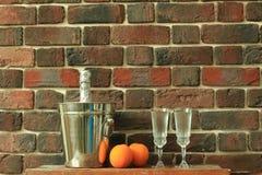Gläser mit Champagner und einem Eimer mit einer Flasche Champagner Stockfotos