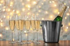 Gläser mit Champagner und Flasche im Eimer auf Tabelle stockbild