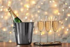 Gläser mit Champagner und Flasche im Eimer auf Tabelle lizenzfreies stockfoto