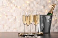 Gläser mit Champagner und Flasche im Eimer auf Tabelle lizenzfreies stockbild