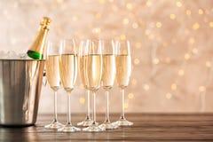 Gläser mit Champagner und Flasche im Eimer auf Tabelle lizenzfreie stockfotografie