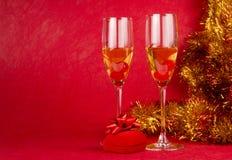 Gläser mit Champagner und Geschenk auf Rot Stockbild
