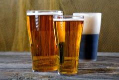Gläser mit dunklem und hellem Bier auf einer Tabelle Stockbild