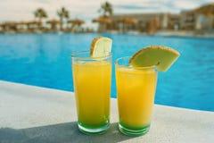 Gläser mit gelbem und grünem Cocktail vor einem schwimmenden PO Stockfoto