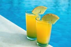 Gläser mit gelbem und grünem Cocktail vor einem schwimmenden PO stockfotos