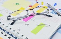 Gläser mit Post-Itanmerkungen und Stift von der Geschäftstagebuchseite Lizenzfreie Stockfotografie