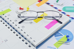 Gläser mit Post-Itanmerkungen und Stift von der Geschäftstagebuchseite Stockfotografie