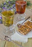 Gläser mit verschiedenen Kräutertees und Plätzchen Stockbild