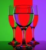 Gläser mit Wasser auf einem bunten Hintergrund Lizenzfreies Stockfoto
