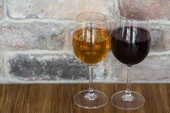 Gläser Rot und Weißwein auf rustikalem Backsteinmauerhintergrund mit Kopienraum Lizenzfreie Stockfotos