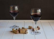 Gläser Rotwein und Korken auf einem weißen Holztisch Lizenzfreie Stockbilder
