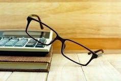 Gläser setzten an Taschenrechner und braunes Farbnotizbuch Stockfotografie