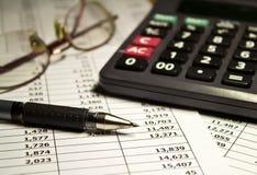 Gläser, Taschenrechner und Stift auf Papier Stockbild
