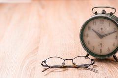 Gläser und alte Uhr auf hölzerner Tabelle Lizenzfreies Stockfoto
