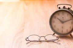 Gläser und alte Uhr auf hölzerner Tabelle Stockbilder