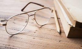 Gläser und Bleistift und alte Bücher auf hölzernem Tabellenhintergrund Stockfoto