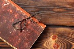 Gläser und Buch auf hölzernem Hintergrund stockfoto